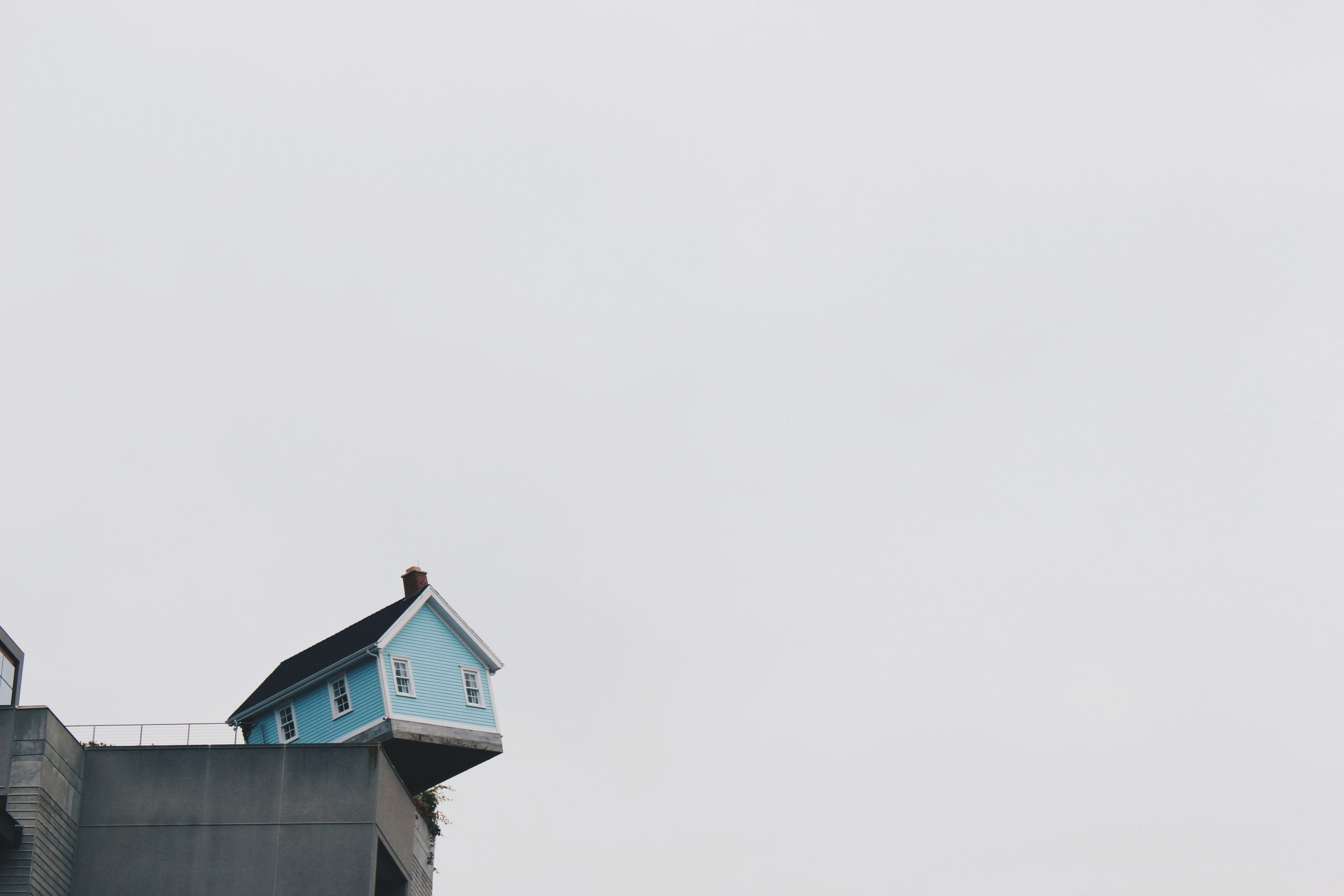 Photo of small blue house perched on edge of a cement dock.