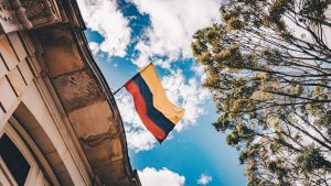 Image of Colomnbian flag flying against a blue sky.