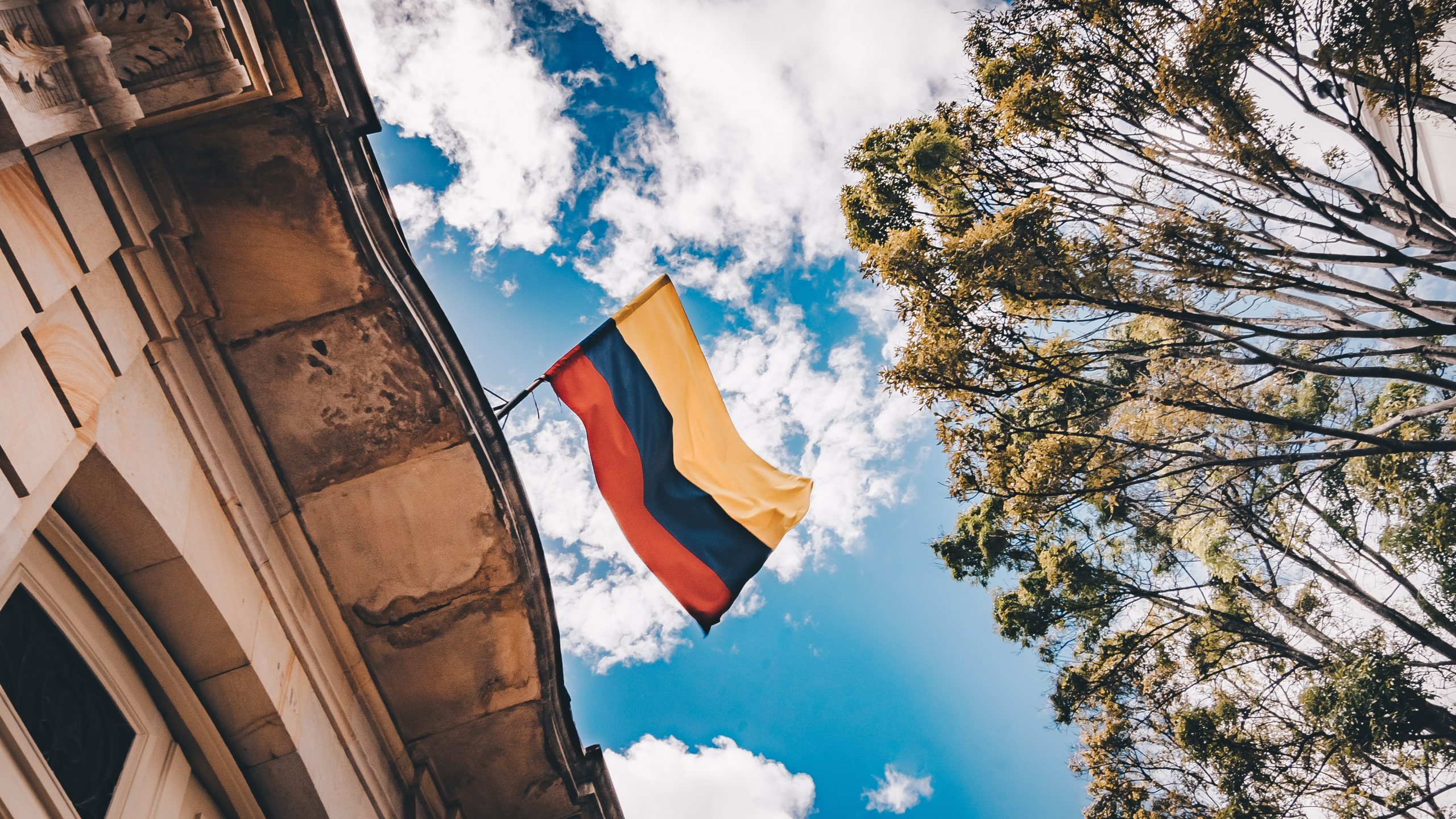 Image of Colomnbian flag flying against a blue sky.