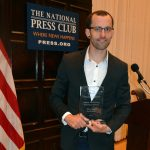 Shane Bauer holding the Anthony Shadid Award for Journalism Ethics at the 2017 award ceremony at the National Press Club in Washington, DC.