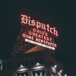 """Night shot of lit sign reading """"Dispatch: Ohio's Greatest Home Newspaper, 145 Years of Service"""""""
