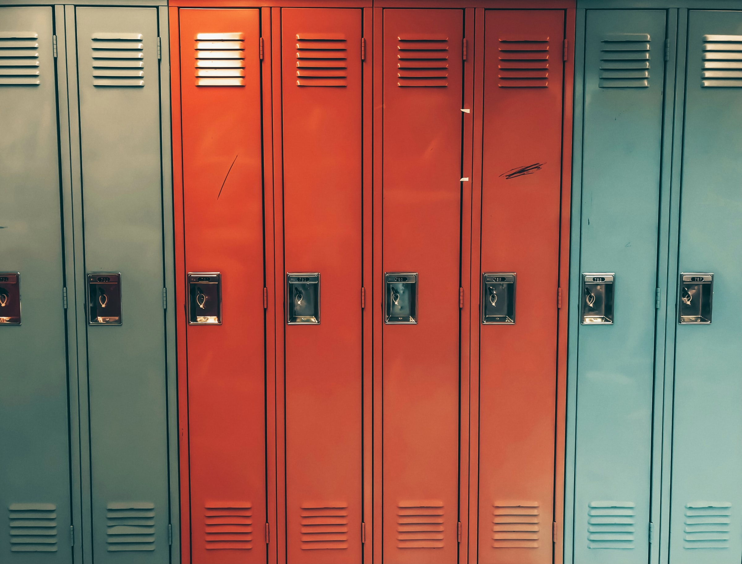 This image shows a series of school lockers in aqua and red.